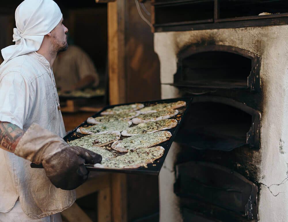 Giacca da cuoco, indossata da un cuoco professionista intento da infornare le pizze
